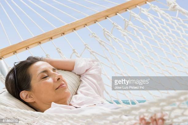 hispanic woman laying in hammock - one mature woman only stock pictures, royalty-free photos & images