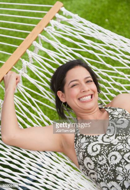 hispanic woman laying in hammock - une seule femme d'âge moyen photos et images de collection