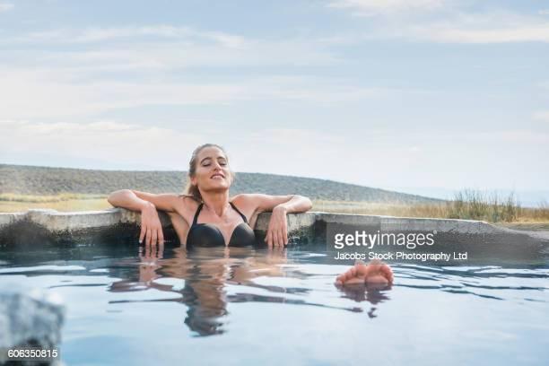 Hispanic woman laying in pool