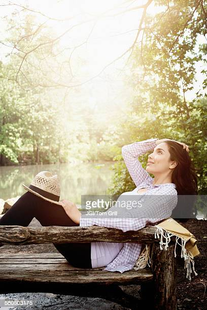 Hispanic woman laying on bench in park