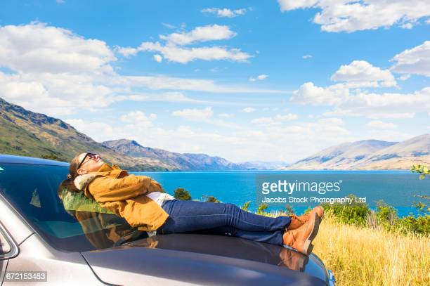 Hispanic woman laying on hood of car at mountain lake napping