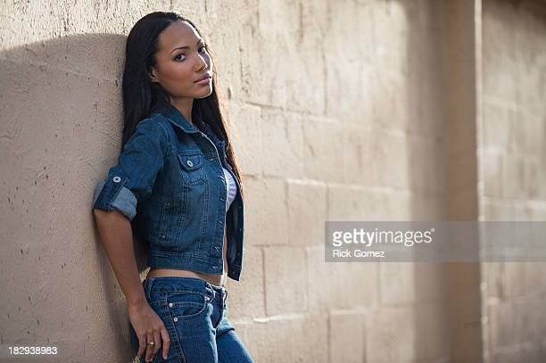 hispanic woman leaning against wall - dominican ethnicity stock photos and pictures