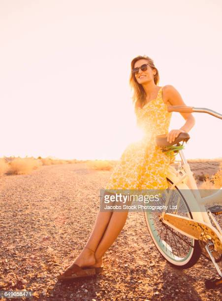 hispanic woman leaning on bicycle on dirt road - yellow dress stock pictures, royalty-free photos & images
