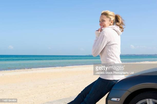 hispanic woman leaning on car enjoying beach - もたれる ストックフォトと画像