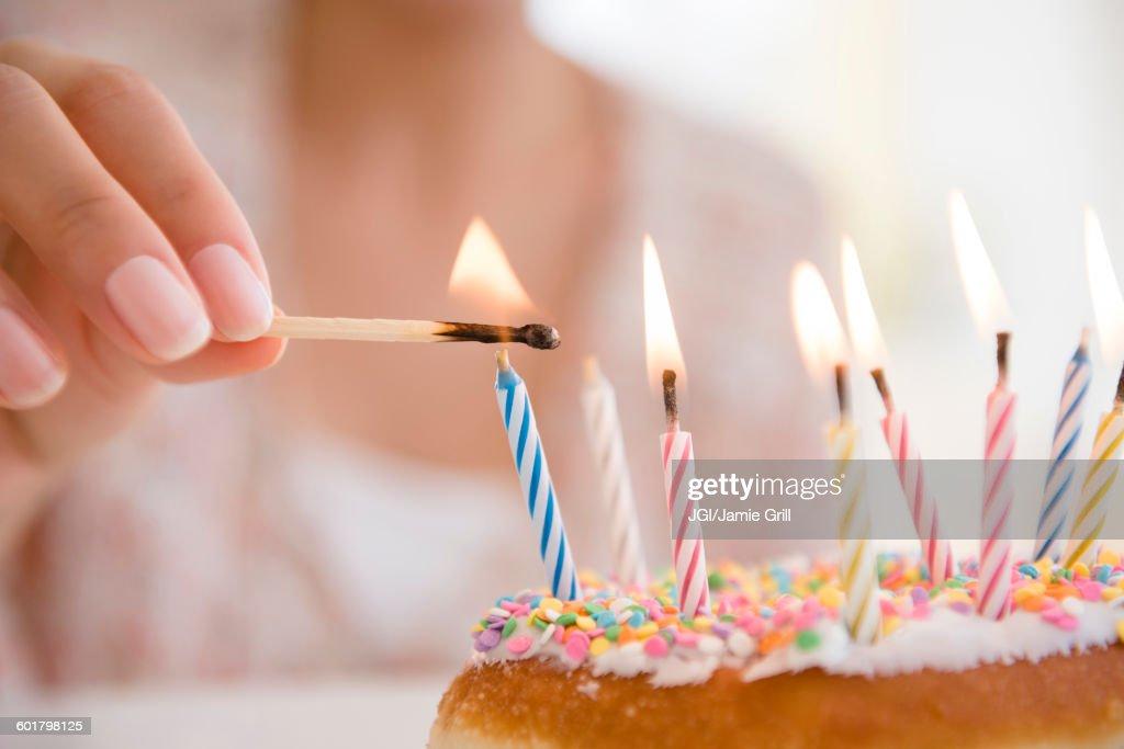 Hispanic woman lighting birthday candles : Stock Photo