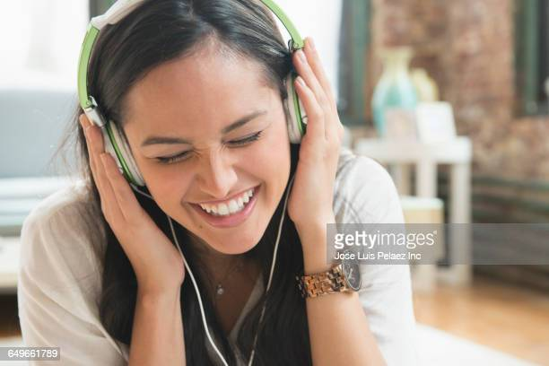 Hispanic woman listening to headphones in living room