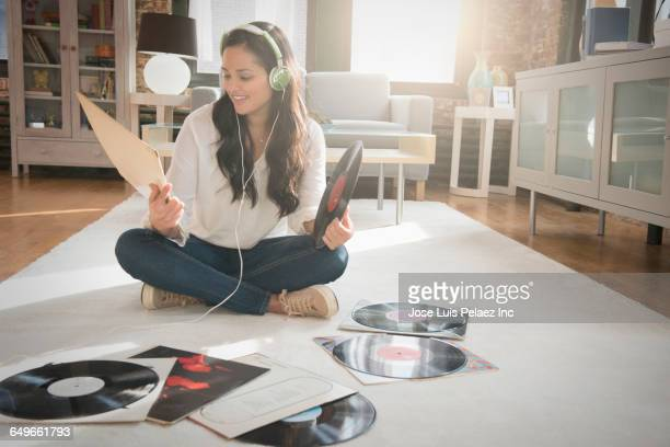 Hispanic woman listening to records in living room