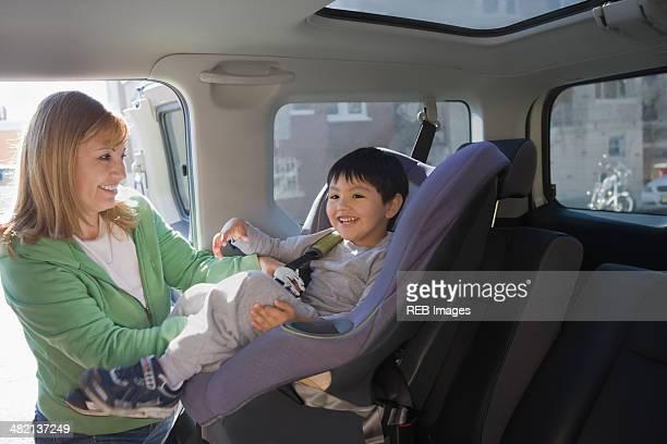 Hispanic woman loading son into car seat