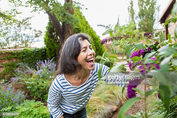 Hispanic woman looking at flowers in garden