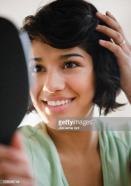 Hispanic woman looking at hair in mirror