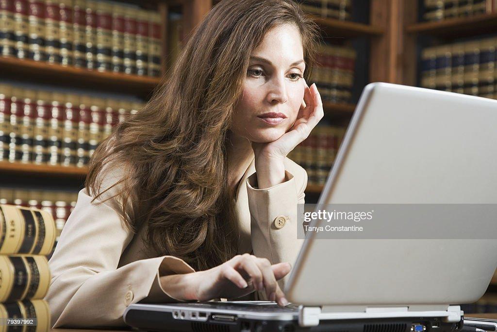 Hispanic woman looking at laptop : Stock Photo