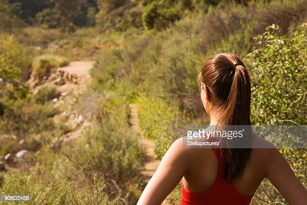 Hispanic woman looking at nature trail