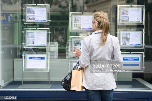 Hispanic woman looking at real estate sign