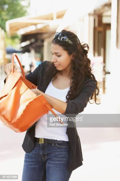 Hispanic woman looking in purse
