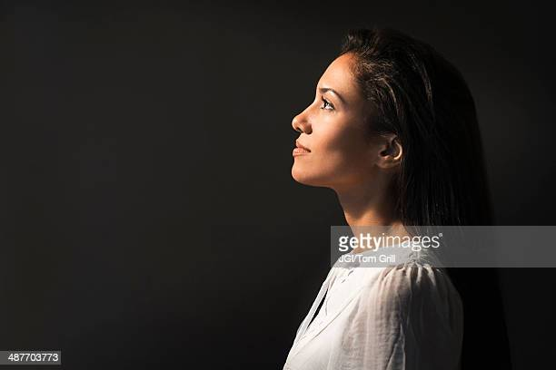 hispanic woman looking up into light - van de zijkant stockfoto's en -beelden
