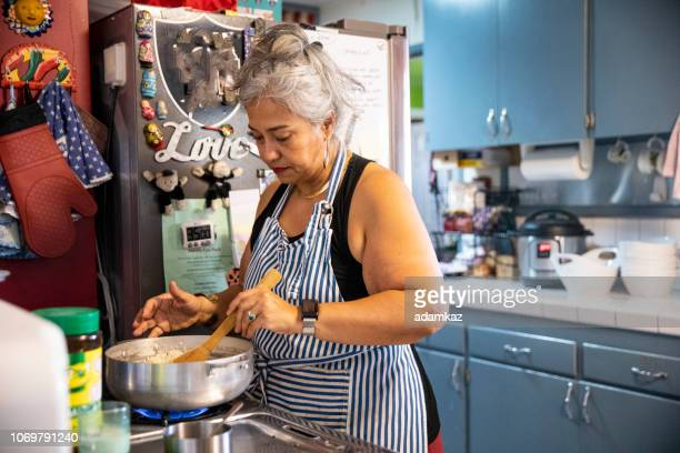 hispanic woman making dinner in kitchen - fat nutrient stock pictures, royalty-free photos & images