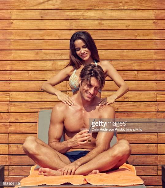 Hispanic woman massaging shoulders of boyfriend outdoors