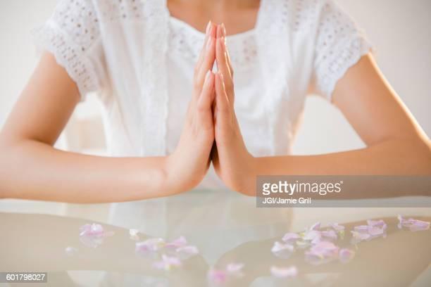 Hispanic woman meditating at table