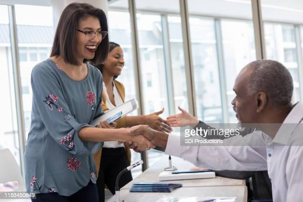 hispanic woman meets her favorite speaker during meet and greet - exhibition stock pictures, royalty-free photos & images
