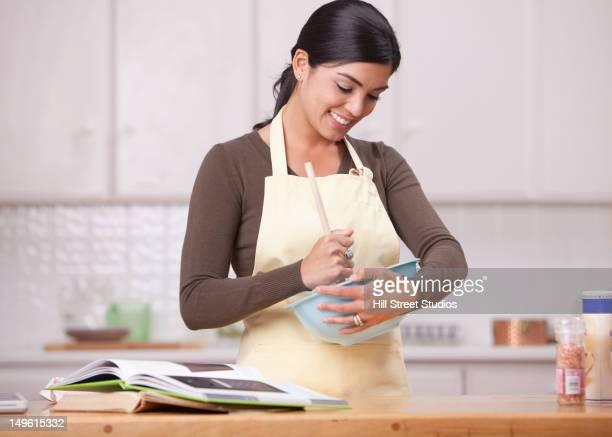 Hispanic woman mixing batter in bowl in kitchen