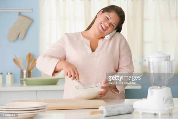 Hispanic woman mixing batter