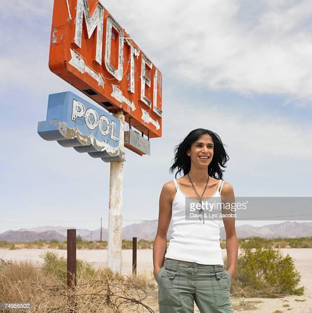 Hispanic woman next to motel sign on beach