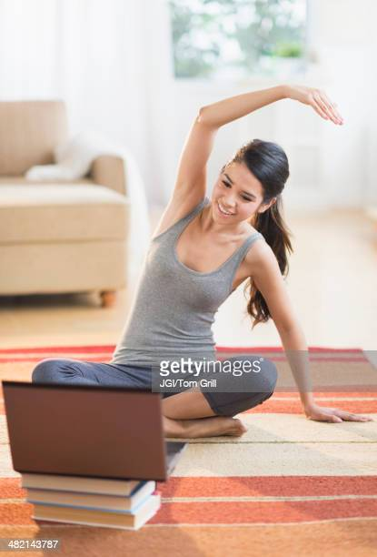 hispanic woman on rug stretching in front of laptop - mood stream stock pictures, royalty-free photos & images