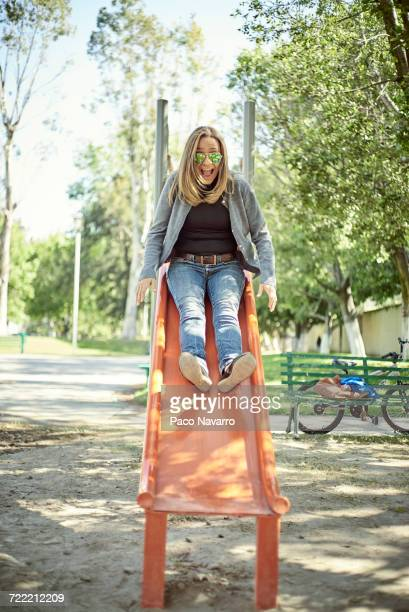 Hispanic woman on slide at playground