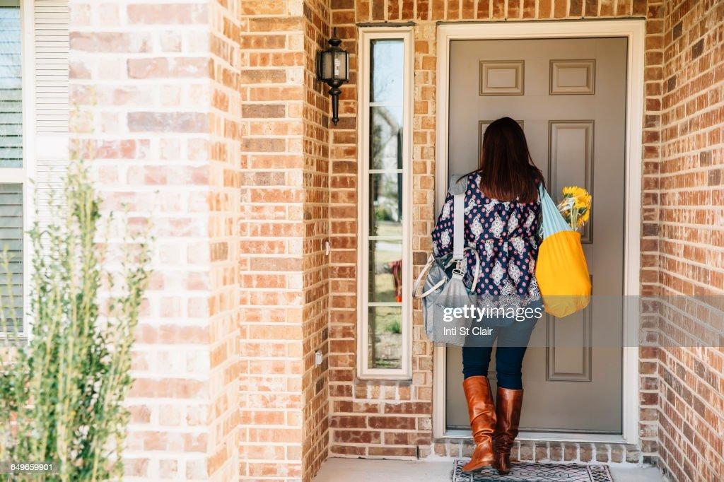 Hispanic woman opening front door : Stock-Foto