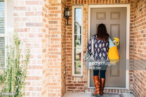 hispanic woman opening front door - ankunft stock-fotos und bilder
