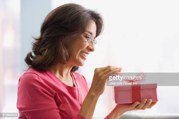 hispanic woman opening gift - birthday present stock pictures, royalty-free photos & images