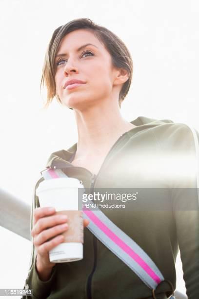 Hispanic woman outdoors with coffee