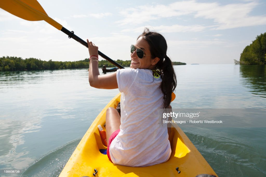 Hispanic woman paddling kayak : Stock Photo