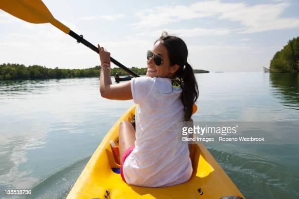 hispanic woman paddling kayak - canoe stock pictures, royalty-free photos & images