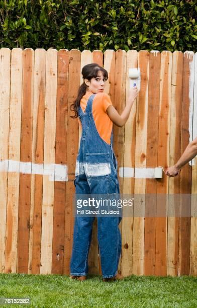 hispanic woman painting fence - bricolage humour photos et images de collection