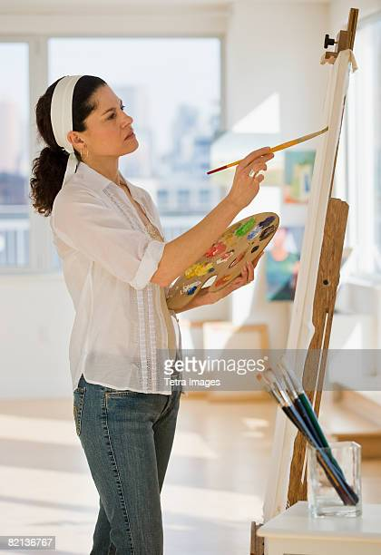 hispanic woman painting on easel - artist's canvas stock pictures, royalty-free photos & images