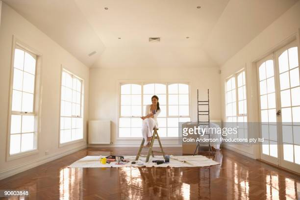 Hispanic woman painting room