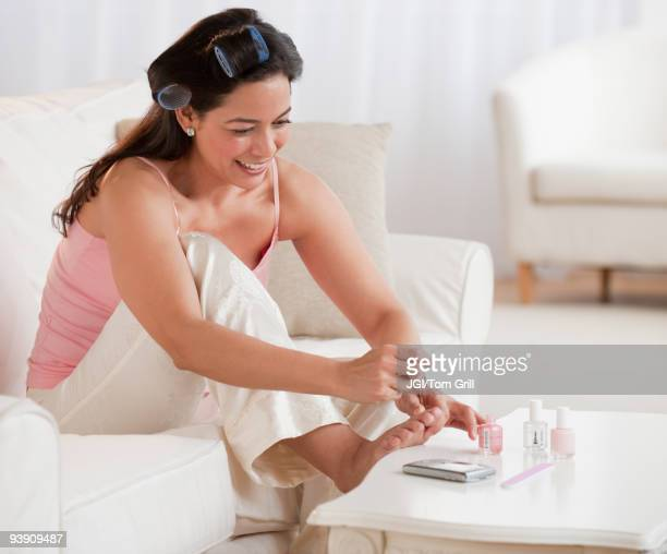 Hispanic woman painting toenails on sofa