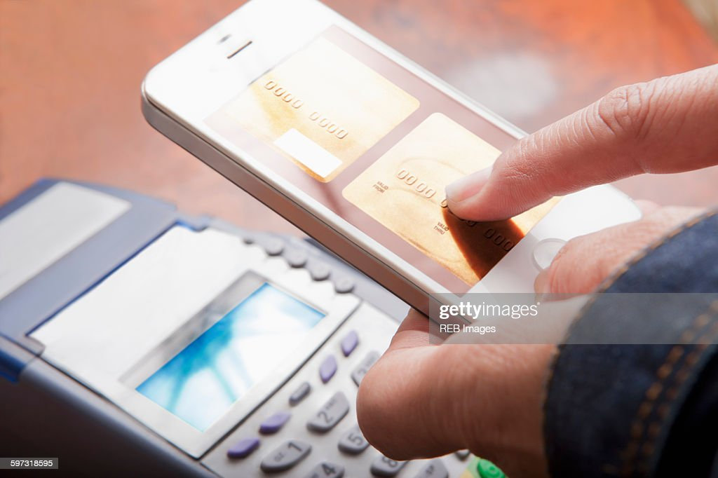 Hispanic woman paying with cell phone : Stock Photo