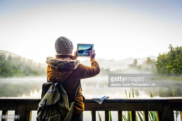 Hispanic woman photographing foggy mountain lake with digital tablet
