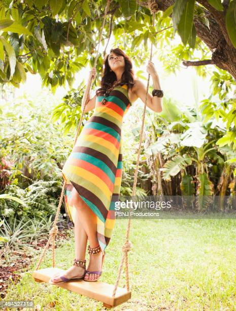 hispanic woman playing on tree swing - striped dress stock pictures, royalty-free photos & images