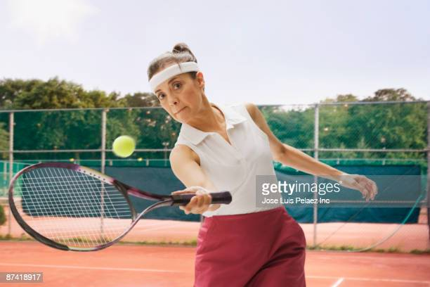 Hispanic woman playing tennis