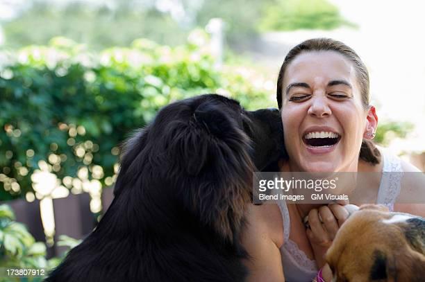 Hispanic woman playing with dogs