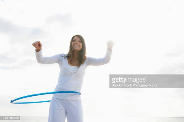 Hispanic woman playing with hula hoop