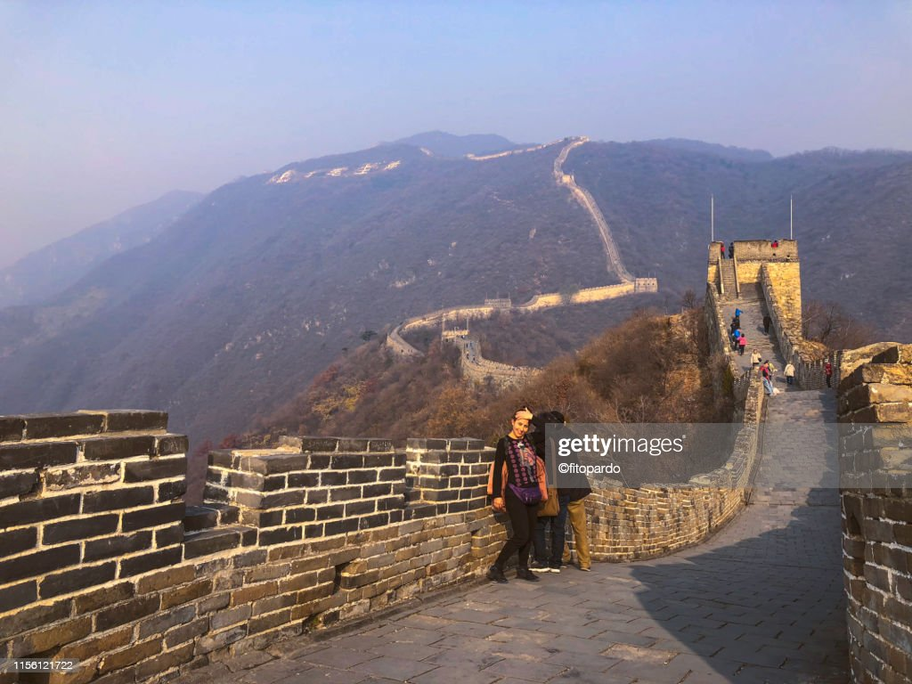 A Hispanic Woman Poses In Front Of The Great Wall Of China High