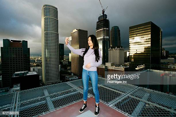 Hispanic woman posing for cell phone selfie on urban rooftop