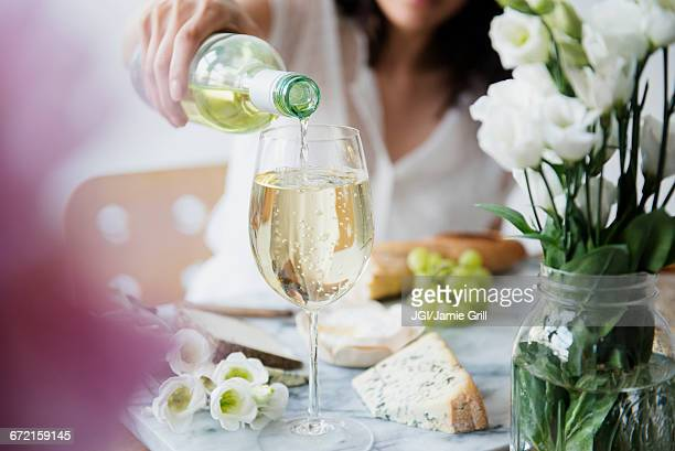 hispanic woman pouring wine at table - white wine stock pictures, royalty-free photos & images