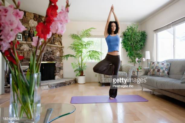 Hispanic woman practicing yoga in living room