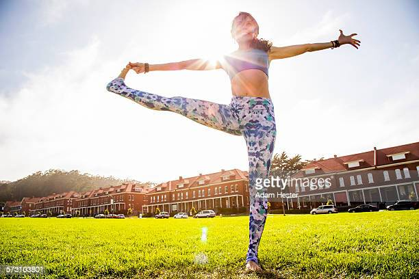 Hispanic woman practicing yoga in urban park