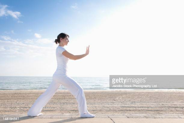 Hispanic woman practicing yoga on beach